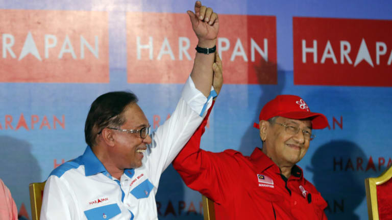 Malaysia's Prime Minister Mahathir Mohamad, right, raises hand of Malaysia's reform icon Anwar Ibrahim during a rally in Port Dickson, last week.