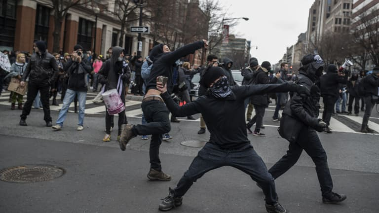Rioters in Washington, DC, throw rocks during a protest on January 20, 2017 - inauguration day.