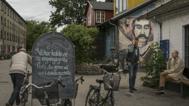 Men speak next to graffiti depicting Mexican revolutionary Emiliano Zapata, outside a bar in Christiania Freetown in the centre of Copenhagen.