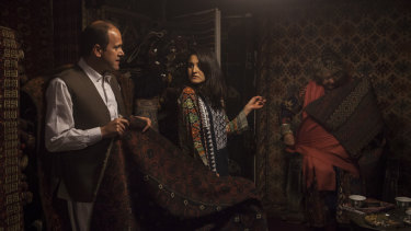 Wahid Abdullah, left, shows foreign customers rugs in his shop, Herat Carpets, on Chicken Street in Kabul, .