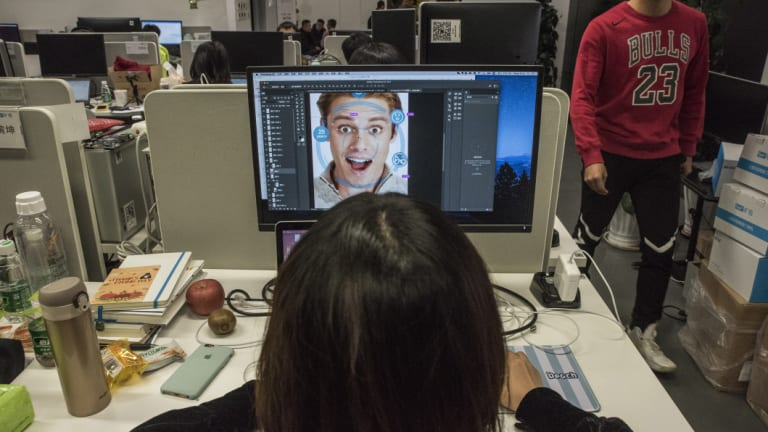At Megvii offices in Beijing, a designer prepares marketing material for a facial-recognition product. The company said Megvii's Face program has helped police make thousands of arrests.