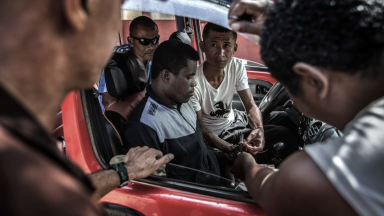 Commissionaires trade vanilla from a vehicle in Sambava.