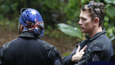 Australian Federal Police and Defence Force personnel talk each other near a cave complex where 12 boys and their soccer coach went missing, in Mae Sai, Chiang Rai province, in northern Thailand.