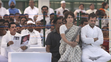 Congress Party president Rahul Gandhi, right, with his sister and party general secretary Priyanka Gandhi Vadra sit as her husband Robert Vadra, left, reads a booklet on Rajiv Gandhi on the anniversary of his death.