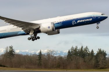 As the Olympic Mountains loom in the distance, the Boeing 777X takes off on its inaugural flight from Paine Field in Everett, Wash, Saturday, Jan. 25, 2020. According to Boeing, the 777X features giant carbon-composite wings, the largest Boeing has ever designed. (Mike Siegel/The Seattle Times via AP)