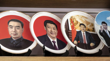Porcelain plates featuring portraits of former Chinese leader Zhou Enlai, left, and Chinese President Xi Jinping are displayed in a shop window in Beijing.
