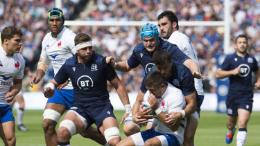 Squaring up: France's Thomas Ramos is tackled by Scotland's Sean Maitland at Murrayfield Stadium.