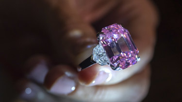 A Christie's employee displays an 18.96-carat fancy vivid pink diamond during a preview.