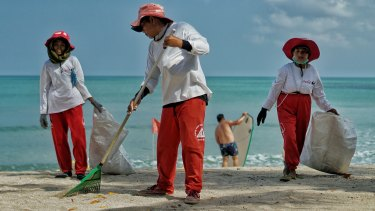 The Kuta Beach cleaners use rakes and gloves to collect the waste that washes onto the beach's white sand shore.
