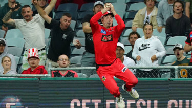 Shaun Marsh of the Renegades takes a catch on the boundary but throws it back into play.