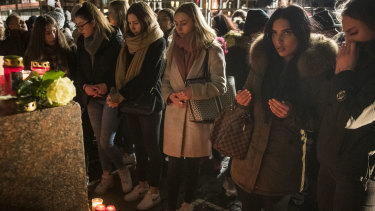 People place candles and flowers at the Brueder Grimm monument after a vigil for the victims near the Midnight shisha bar.