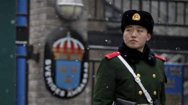 A paramilitary police officer stands guard at the gate of the Swedish Embassy in Beijing.