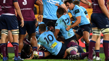 Against the odds: Kurtley Beale scores for the embattled Waratahs in the win over the Reds.