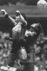 "Diego Maradona beats English goalkeeper Peter Shilton to a high ball and scores the ""hand of God""."
