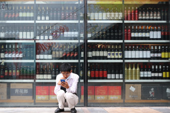 A man sits in front of a wine shop that sells Australian wines in eastern Beijing's Tongzhou district.