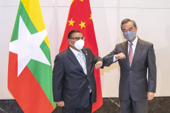 China's Foreign Minister Wang Yi at right bumps elbows with with Myanmar's Foreign Minister U Wunna Maung Lwin in Chongqing, China on June 8, 2021. Beijing abstained from the UN vote condemning the junta.