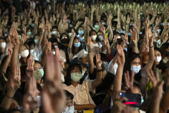 Students raise a three-finger salute, a resistance symbol borrowed from the 'The Hunger Games', during a protest at Thammasat University on Monday.