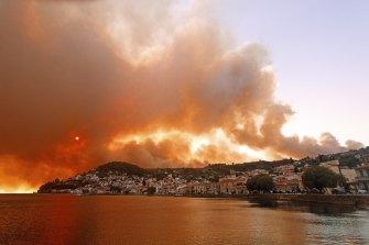Flames burn on the mountain near Limni village on the island of Evia.