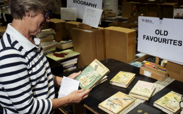 Lifeline volunteer Judy Nicholls examines one of the Fleming first editions.