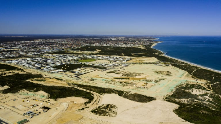 This drone shot shows a south-facing view of Alkimos Beach near Yanchep. Perth's skyline is just visible on the horizon, and the stretch of the coastal suburbs can be seen clearly.
