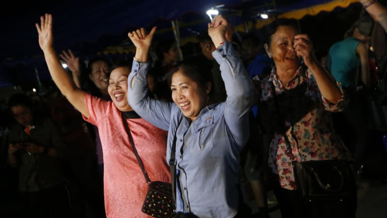 People celebrate after divers evacuated some of the 12 boys and their coach trapped at Tham Luang cave.