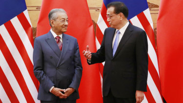 Malaysian Prime Minister Mahathir Mohamad, left, and his Chinese counterpart Li Keqiang chat during a signing ceremony.