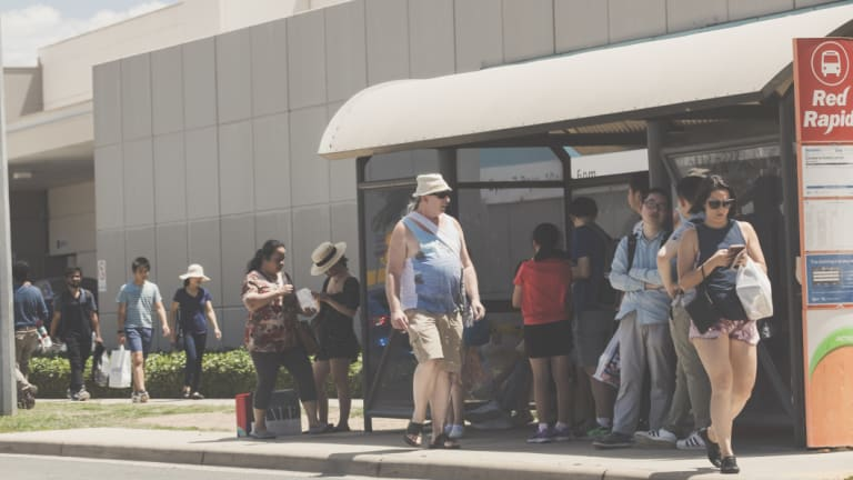 Boxing Day sales crowds wait for a bus on Iron Knob Street outside the Canberra Outlet Centre in Fyshwick.
