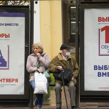 People wait at a St Petersburg bus stop decorated with election posters in September.