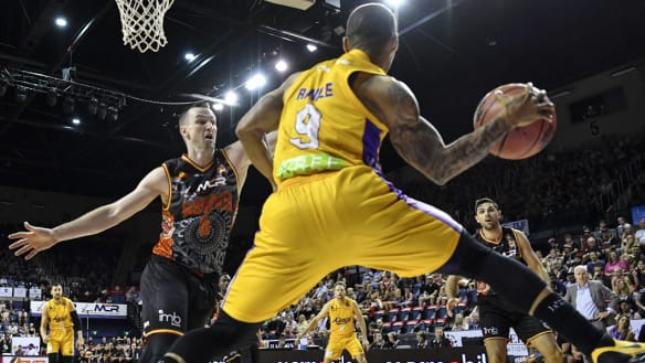 Peripheral vision: Jerome Randle seeks to pass around Andrew Ogilvy of the Hawks at the WIN Entertainment Centre.