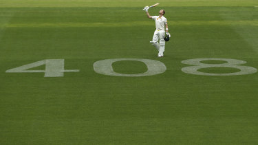 Smith raises his bat to the sky after reaching a century against India at Adelaide.