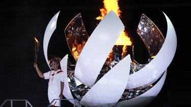 Japan's Naomi Osaka reacts after lighting the cauldron.