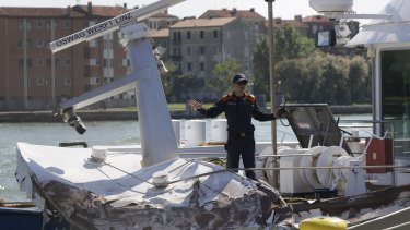 Italian Coast Guard officers inspect a tourist boat that was struck by the cruise ship.