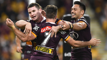 Broncos players celebrate during their win over the Cowboys on Friday night at Suncorp Stadium.