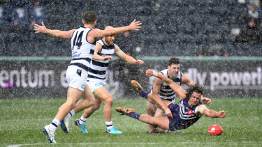 Fremantle's Brady Grey battles a pack of Cats and the wet conditions.