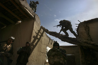 Australian soldiers search a house for weapons, explosives and Taliban fighters during a foot patrol in Chora, Afghanistan, in 2009.