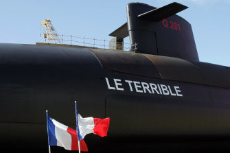 """French flags fly during the launch of the country's  nuclear-powered submarine, """"Le Terrible"""", in Cherbourg. There have been terrible ructions between France and Australia since the AUKUS alliance was announced."""