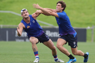 Josh Bruce (left) in a contest with Patrick Lipinski at Bulldogs training on Monday.