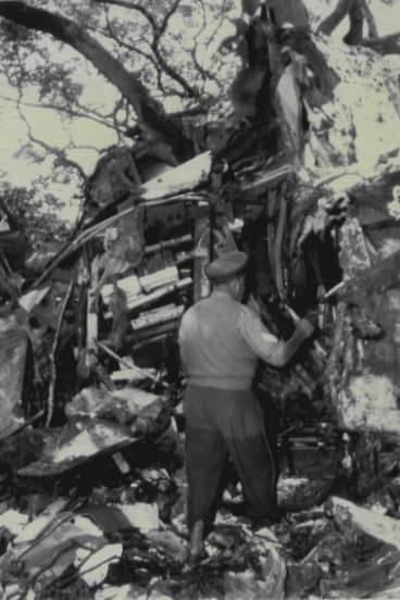 A policeman, trousers wet to his thighs, inspects the aircraft wreckage at Bulwer Island, in which two crew members died.