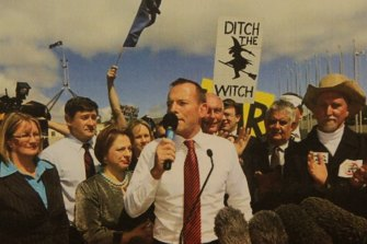 Then-opposition leader Tony Abbott addresses an anti-carbon tax rally in 2011, amid posters vilifying Gillard as prime minister.