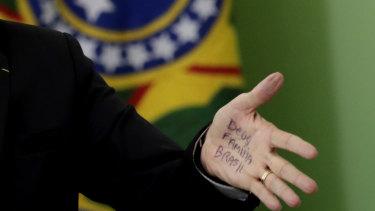 "Brazil's Evangelical President Jair Bolsonaro's hand shows notes that read in Portuguese ""God, Family, Brazil"", during a speech in Brasilia last week."
