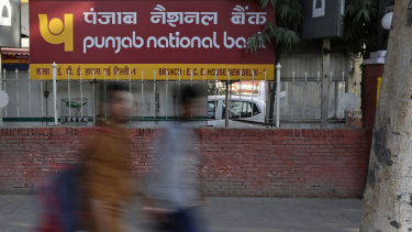 Pedestrians walk past a sign board of Punjab National Bank in New Delhi, India.
