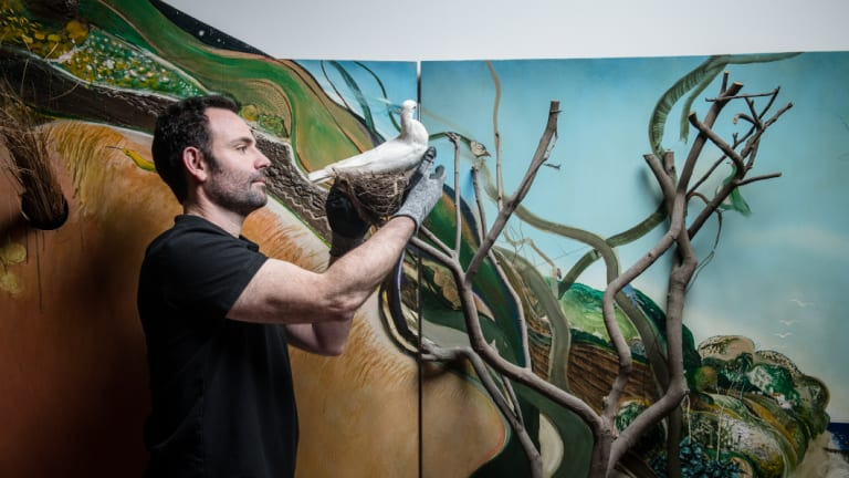 Giovanni Di Dio, acting manager of exhibitions at Art Gallery of Western Australia, installing Brett Whiteley's The American Dream.