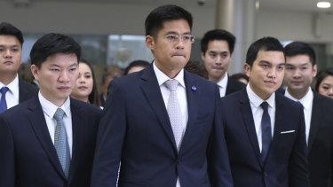 Leader of the Thai Raksa Chart party Preechapol Pongpanich, centre, leaves the Constitutional Court in Bangkok on Thursday.