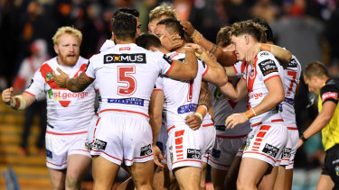 Back on track: Tyson Frizell is mobbed by teammates after scoring.
