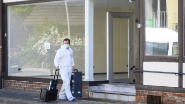 A crime scene officer arrives at an apartment in Wittingen where the bodies of two women were found on Monday.