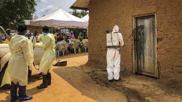 A worker from the World Health Organisation decontaminates the doorway of a house on a plot where two cases of Ebola were found in the village of Mabalako, eastern Congo.