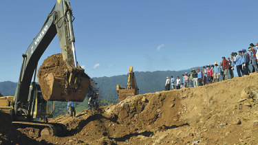 Excavators dig through soil to search for bodies of miners as workers and rescue members gather in Hpakant, Kachin State, Myanmar, in 2015 when landslides killed at least 116.