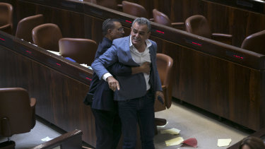 A Knesset usher removes Jamal Zahalka, an Israeli Arab member of the Knesset representing the Balad party, who was protesting against the passage of the bill.