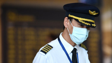 An airline crew member wears a mask at Brisbane International Airport in January.