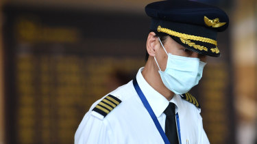 A pilot wearing a mask at Brisbane International Airport in January. Airlines are working out what precautions to put in place as travel demand slowly returns.